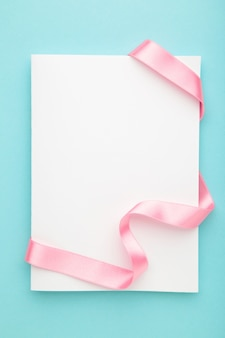 Card note with pink ribbon on blue pastel surface