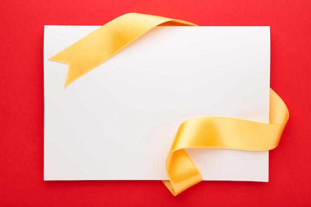 Card note with shiny gold ribbon on red background. top view.