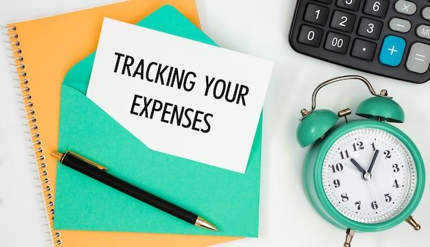 Карточка на почтовом конверте с текстом отслеживание расходов, часы, калькулятор, ручка.