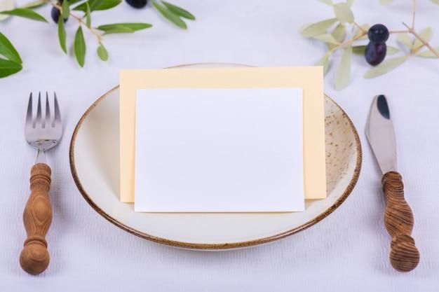 カードまたは招待状、メニュー、オリーブの枝を持つ磁器プレートにカードを配置するためのメモ Premium写真