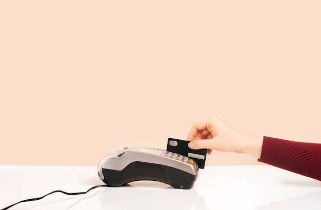 Card payment concept bar counter and hand on a pink background terminal for payments