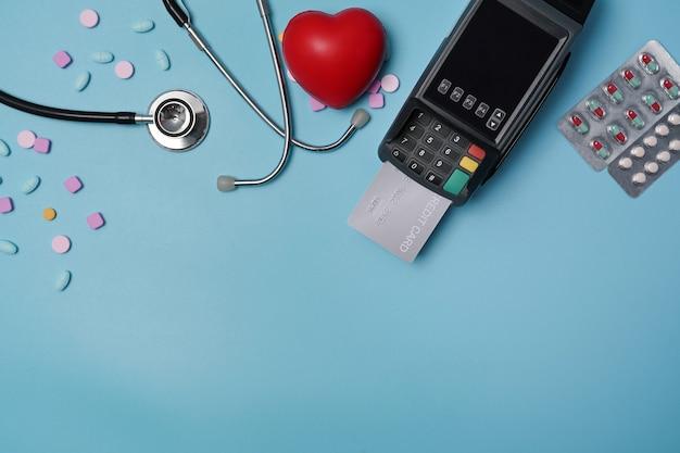 青の背景にカード決済機、聴診器、ピルブリスターパック。
