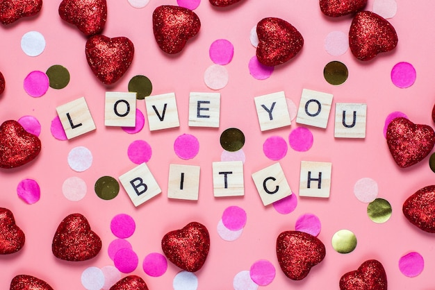 Card for valentine's day. on a pink background wooden letters lined with love you bitch. funny congratulations. flat lay, top view.