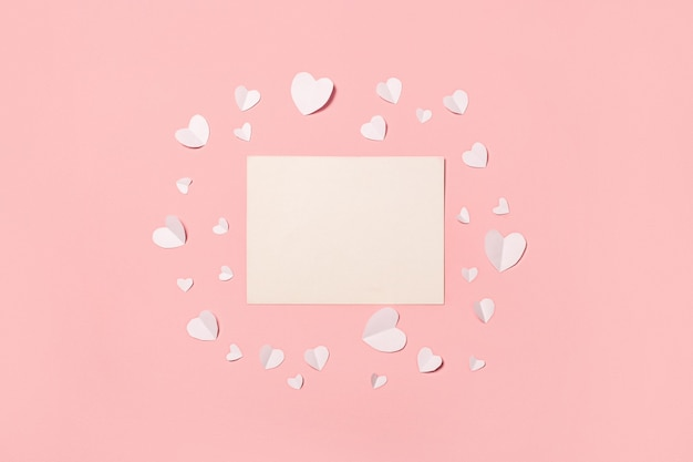 Card and white paper hearts on a pink background. composition valentine's day. banner. flat lay, top view.