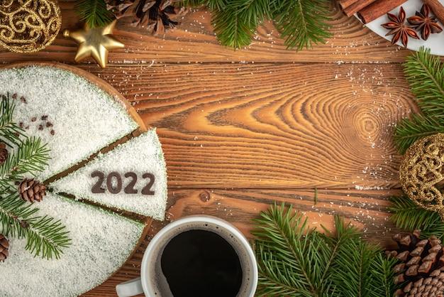 초콜릿으로 만든 숫자 2022로 장식된 흰색 축제 케이크와 커피 한 잔이 있는 카드. 새 해의 개념입니다. 복사 공간