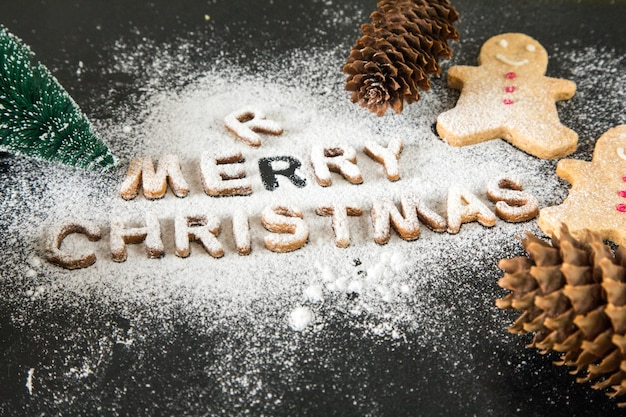 Card with gingerbread cookies. baked letters merry christmas, fir tree. christmas card