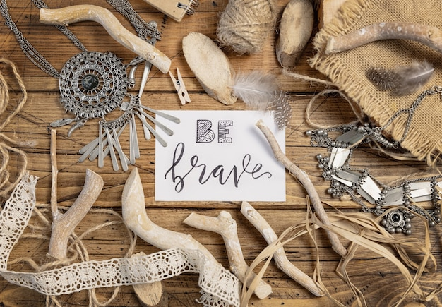 Card with the handwritten text be brave with bohemian decorations around top view on a wooden table