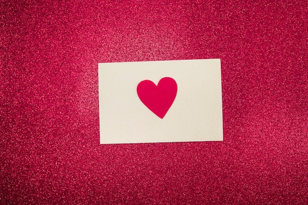 Card with a heart on a pink glittering