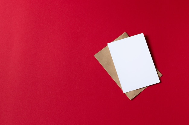Card with kraft brown paper envelope template mock up on red background