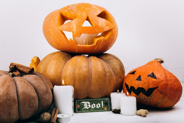 Card with lettering 'boo' stands before scarry halloween pumpkins