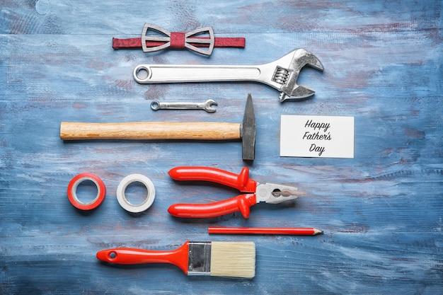 Карточка с текстом «с днем отца», галстуком-бабочкой и набором инструментов на деревянном столе