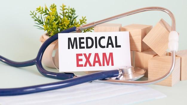 テキスト健康診断、医療コンセプトのカード。 wodenブロック、聴診器、背景の花