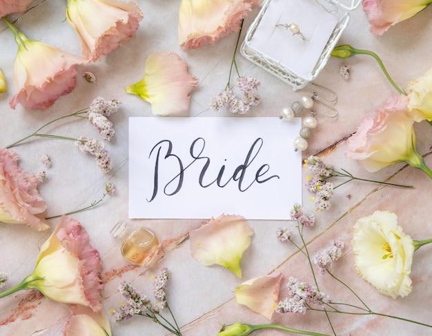 Открытка с рукописным текстом невеста в окружении розовых цветов, сережек, обручального кольца, лепестков и флакона духов на мраморном столе, вид сверху. романтическая концепция