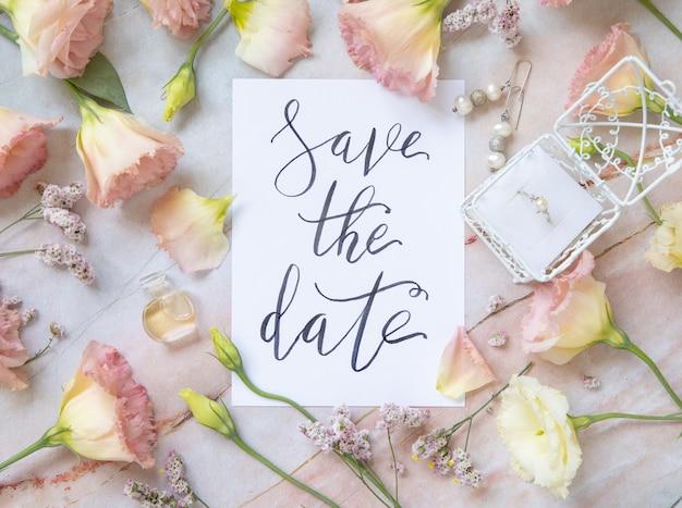 손으로 쓴 텍스트 save the date가 있는 카드는 대리석 테이블에 분홍색 꽃, 귀걸이, 꽃잎 및 퍼퓸 플라콘 상단 보기로 둘러싸여 있습니다. 로맨틱 컨셉