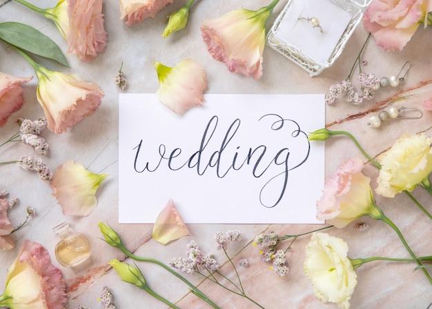 대리석 테이블에 분홍색 꽃, 귀걸이, 꽃잎 및 퍼퓸 플라콘 상단 보기로 둘러싸인 필기 텍스트 wedding이 있는 카드. 로맨틱 컨셉