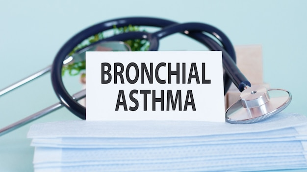 Card with words bronchial asthma, stethoscope, face masks and flower on table on table.