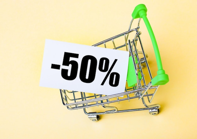 The card with the words minus fifty percent is in the shopping cart. marketing concept.