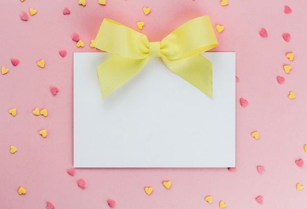 Card with a yellow bow on a background of heart-shaped confectionery confetti on a pink background copy space