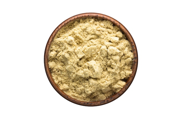 白い背景で隔離の木製ボウルのカルダモンパウダースパイス。調味料上面図