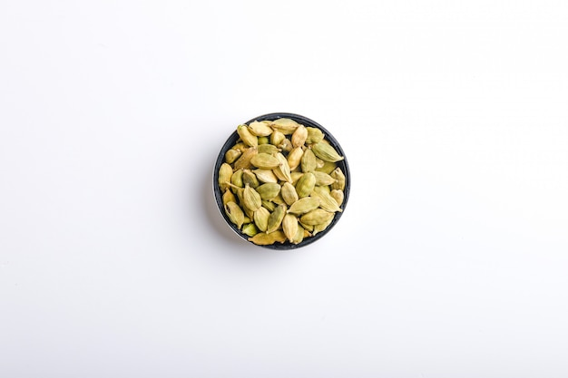 Cardamom seeds in a bowl on a white background