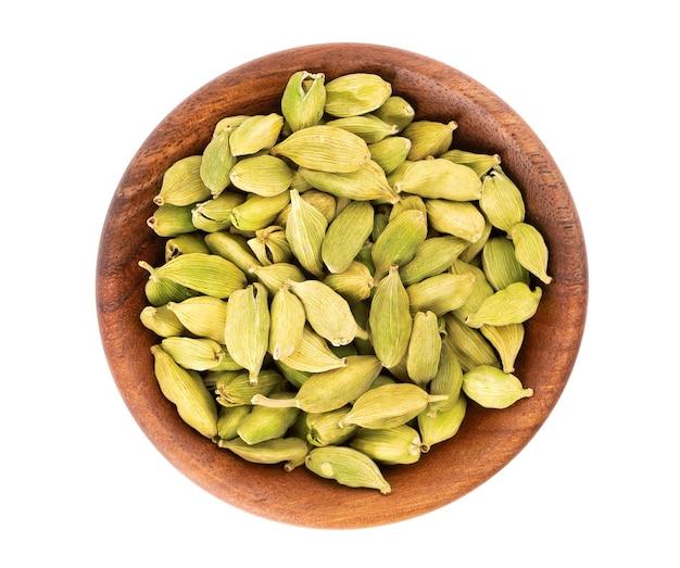 흰색 절연 나무 그릇에 카 다 몬 씨앗. 녹색 카 다몬 더미입니다. 평면도.