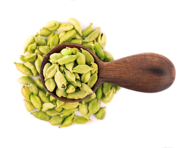 Cardamom seeds in wooden spoon, isolated on white.