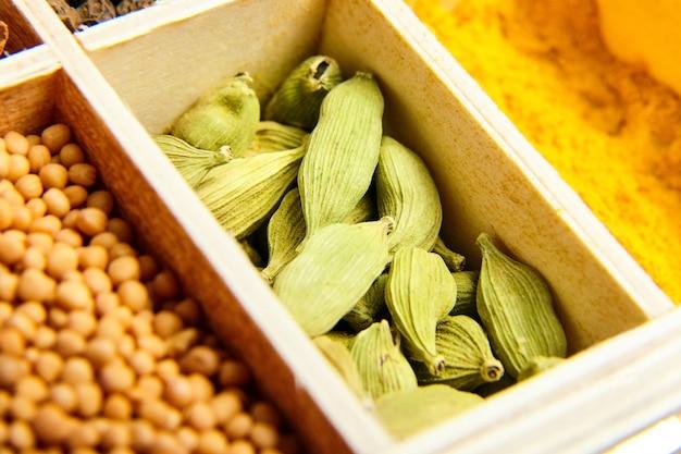 カルダモンの種子。木製トレイのさまざまな乾燥スパイス。マスタードと黄色のウコンまたはウコン