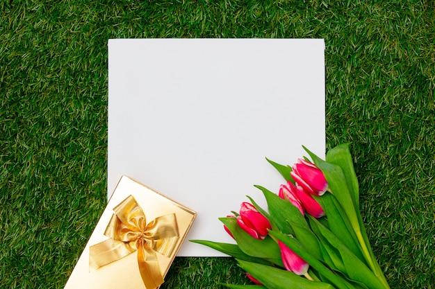 골 판지 및 녹색 잔디에 선물 상자와 튤립