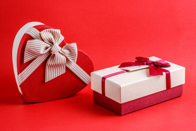 Cardboard biodegradable gift box in the shape of a heart and in the shape of a rectangle with bows on red
