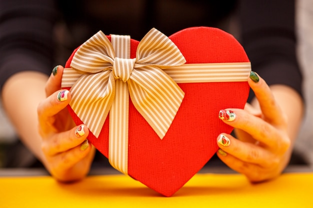 Cardboard biodegradable heart-shaped gift box in women's hands