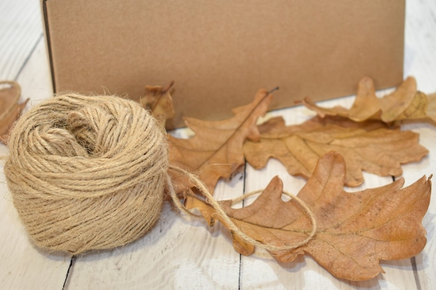 Cardboard box, autumn leaves and ball of rope on background of wooden table top. seasonal delivery