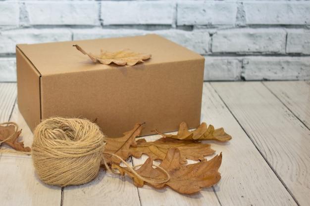 木製のテーブルとレンガの壁の背景に段ボール箱、秋のオークの葉とロープのボール
