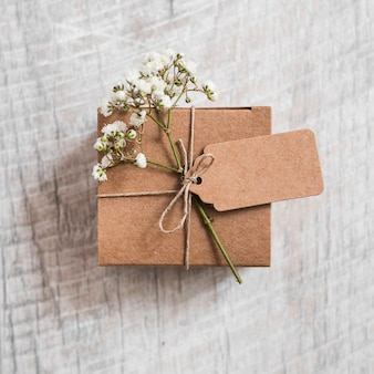 Cardboard box and baby's-breath flower tied with string on wooden backdrop
