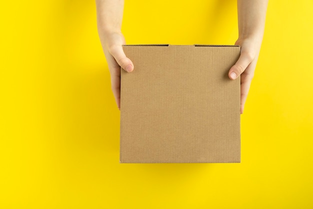 Cardboard box in child hands on yellow background, top view. copy space. mock up.