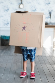 Cardboard box drawn with robot over the boy standing in the room
