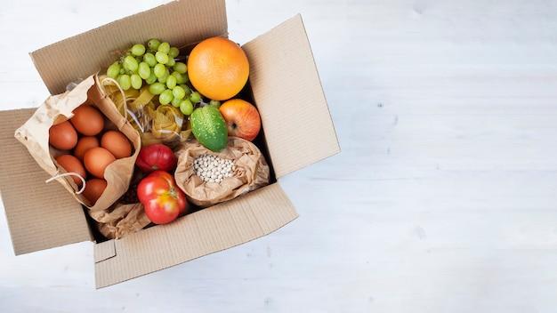 ファーマーズマーケットからの果物野菜豆卵でいっぱいの段ボール箱生態学的な有機食品
