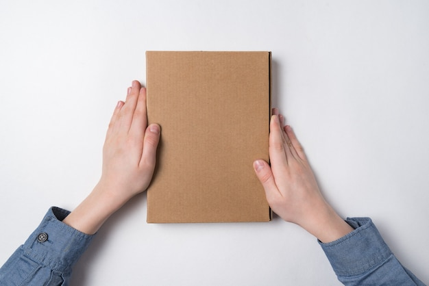 흰색 배경에 어린이 손에 골 판지 상자. 평면도. 공간을 복사하십시오. 프리미엄 사진