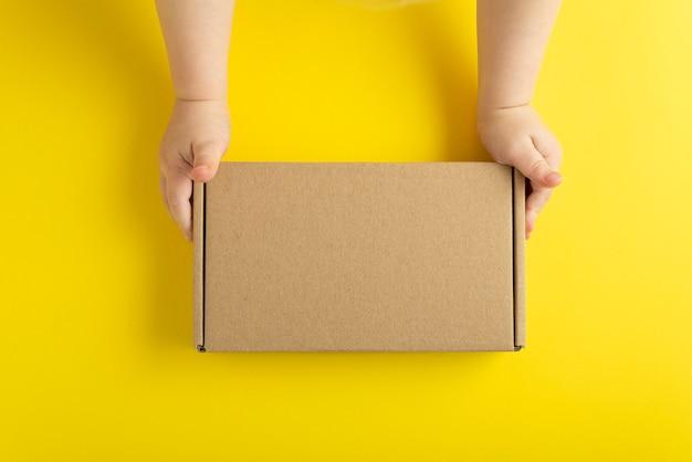 小さな子供の手の段ボール箱。黄色の背景、上面図。モックアップ。