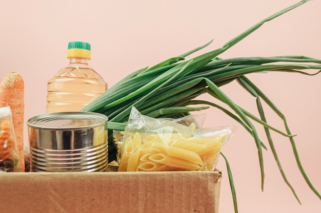 バター、缶詰、玉ねぎ、クッキー、パスタ、果物とピンクの背景に分離された段ボール箱。食品デリバリー。