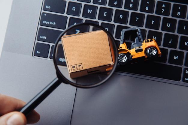판지 상자, 로더 모델 및 돋보기. 인터넷 상거래, 온라인 쇼핑, 무역 및 매출의 개념.