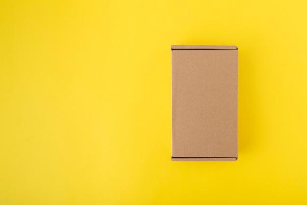 黄色の背景上面図の段ボール箱。クラフト包装。スペースをコピーします。モックアップ