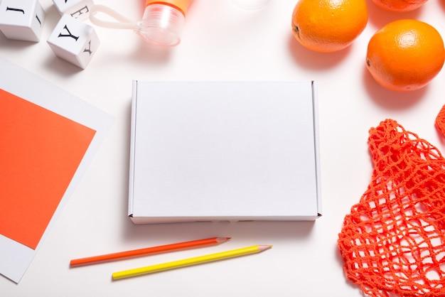 新鮮なオレンジと白の段ボール箱、フラットレイ