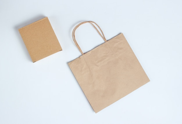 Cardboard box and paper bag on a gray. top view.