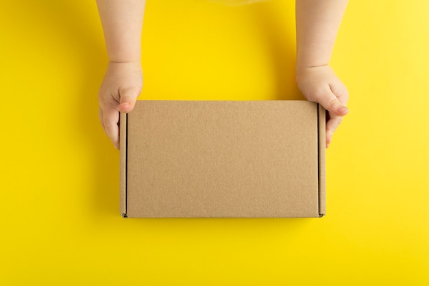 Cardboard box in small childrens hands. yellow background, top view. mock up.