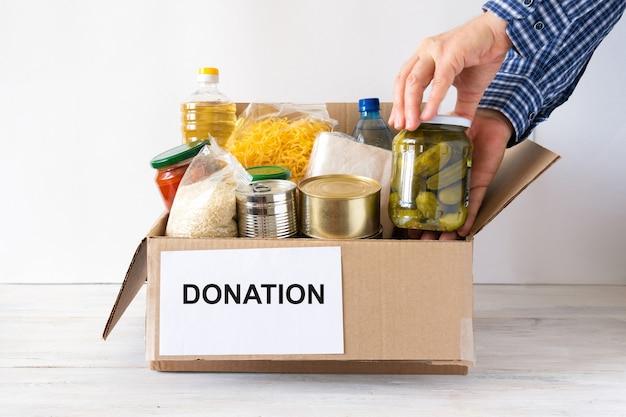 バター、缶詰、シリアル、パスタが入った段ボール箱。さまざまな食料品が入った募金箱。手には食べ物が置かれます。