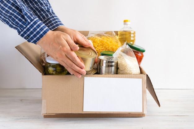 버터, 통조림 식품, 시리얼 및 파스타가 들어있는 판지 상자. 다양한 식품이 담긴 기부 상자. 손에 음식이 놓여 있습니다.