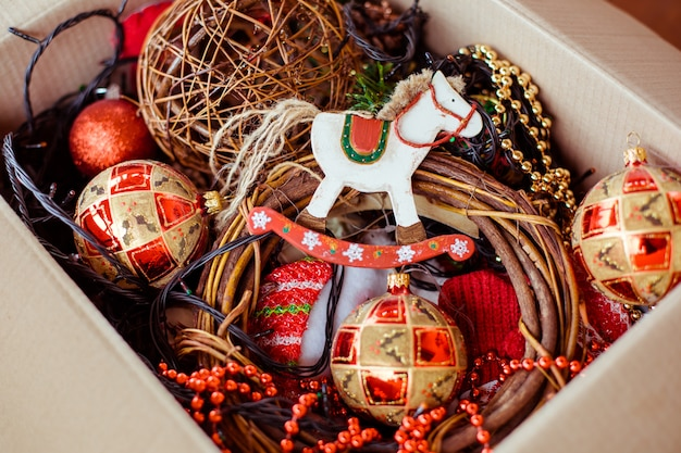 A cardboard box with christmas toys for for decorating christmas tree.