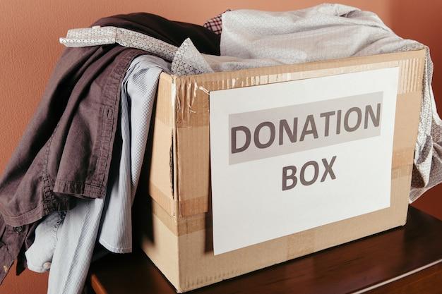 寄付の服と木の上のさまざまなオブジェクト、寄付の概念が入った段ボール箱