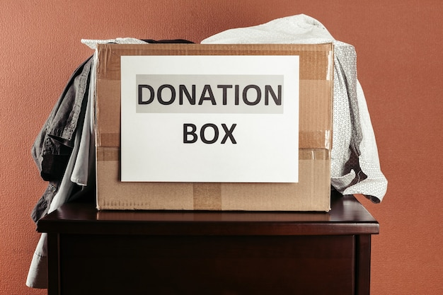Cardboard box with donation clothes and different objects on wood, donation concept