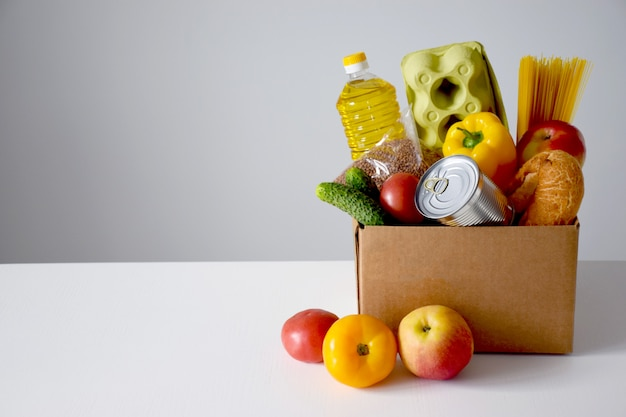Картонная коробка с едой, маслом, хлебом, яйцами, помидорами, яблоками, огурцами, банкой, спагетти